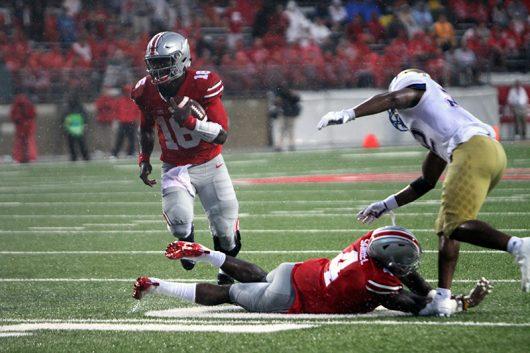 OSU redshirt junior quarterback J.T. Barrett (16) scores his first rushing touchdown of the game during the third quarter against Tulsa on Sept.10. The Buckeyes won 48-3. Credit: Alexa Mavrogianis   Photo Editor