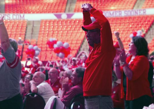 """University President Michael Drake sings along to the Ohio State University Marching Band's rendition of """"Hang On Sloop"""" during Buckeye Bash on Sept. 17 at the Lloyd Noble Center in Norman, Oklahoma. Credit: Alexa Mavrogianis 