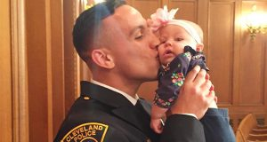 Mike Harrigan, a Cleveland Division of Police officer, kisses his daughter, Kapree, during a ceremony in April at the Cleveland Courthouse. Credit: Courtesy of Mike Harrigan