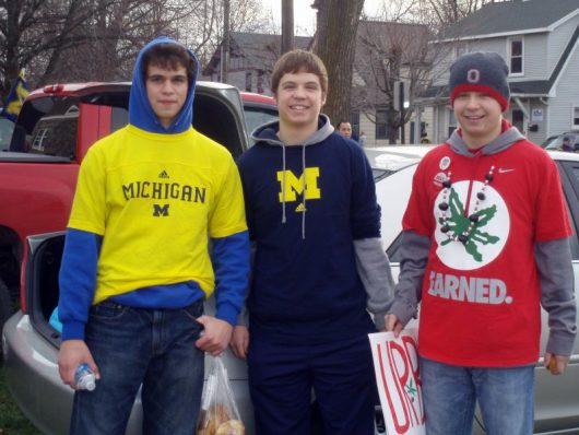 Aaron Tomich (author, right) stands next to brother Matthew (center) and close friend Antonio Carroscia decked in OSU and U of M gear before the 2011 OSU-Michigan game in Ann Arbor, Michigan. Courtesy: Aaron Tomich