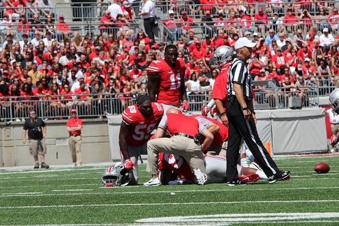 Tracy Sprinkle (93) down on the field, surrounded by players and staff in the first quarter versus Bowling Green on Sept. 3, 2016. Credit: Alexa Mavrogianis | Photo Editor