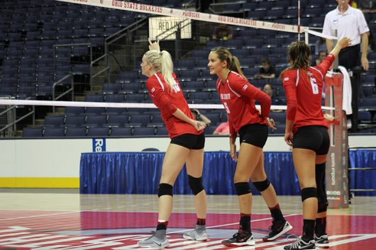 Senior middle blocker Taylor Sandbothe, junior outside hitter Luisa Schirmer and sophomore setter Taylor Hughes gather near the net during a match against LIU Brooklyn. The Buckeyes won 3-0.  Credit: Jenna Leinasars | Assistant News Director