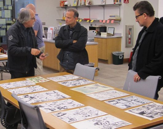 Patrons of Cartoon Crossroads gather around a table with artists' work laid out on it during the show in 2015. Credit: Courtesy of Cartoon Crossroads Columbus