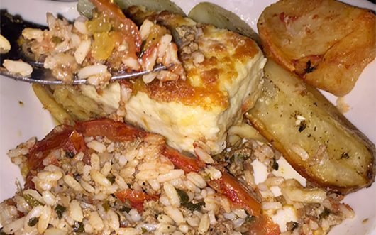 A traditional Greek dish of stuffed tomato, pastitsio and lemon potato. Credit: Elizabeth Tzagournis | Lantern Reporter