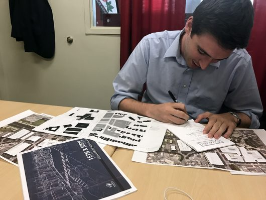 Gerard Basalla, a fourth-year in political science and strategic communication and Undergraduate Student President, looks over plans for the off-campus 15th and High redevelopment plan and on-campus the One Ohio State Framework plan. Credit: Summer Cartwright | Lantern Reporter