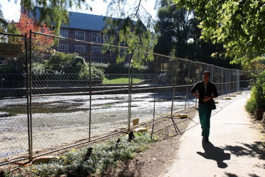 A student walks by Mirror Lake on Oct. 12. Ohio State started draining the lake on Oct. 11. Credit: Nick Roll   Campus Editor