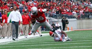 OSU redshirt junior quarterback J.T. Barrett (16) flies through the air to avoid a tackle during the first half of the Buckeyes game against Rutgers on Oct. 1. The Buckeyes won 58-0. Credit: Alexa Mavrogianis   Photo Editor