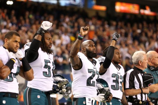 Philadelphia Eagles players Steven Means (51), Malcolm Jenkins (27) and Ron Brooks (33) raise their fists in the air during the national anthem for a game against the Chicago Bears on Sept. 19. Credit: Courtesy of TNS