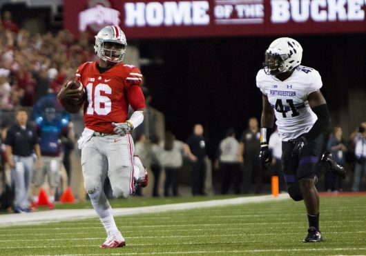 OSU redshirt junior quarterback J.T. Barrett (16) outpaces Northwestern redshirt sophomore safety Jared McGee (41) during the Buckeyes game on Oct. 29. The Buckeyes won 24-20. Credit: Alexa Mavrogianis | Photo Editor