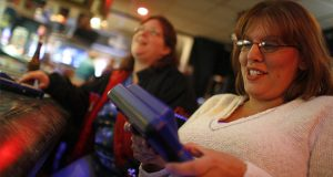 Riverboat Lanes owner Michelle Mona, right, and Jill Buxengard play an Internet trivia game at the alley's bar on November 2, 2006, in Wabasha, Minnesota. (Renee Jones Schneider/Minneapolis Star Tribune/MCT)