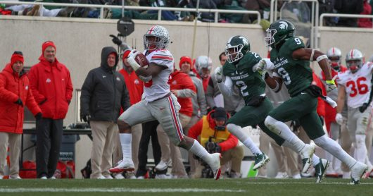 OSU freshman running back Mike Weber (25) outruns two MSU players during their game on Nov. 19, 2016 at Spartan Stadium. The Buckeyes won 17-16. Credit: Mason Swires | Assistant Photo Editor