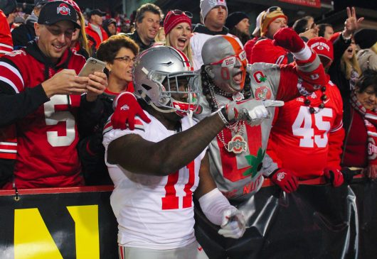 OSU redshirt junior defensive end Jalyn Holmes (11) celebrates with the Big Nut and other Buckeye fans following the Buckeyes 62-3 win over Maryland on Nov. 12. Credit: Alexa Mavrogianis | Photo Editor