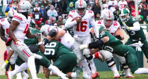 OSU redshirt junior quarterback looks for a lane through the Michigan State defense during the Buckeyes' game against the Spartans. Credit: Alexa Mavrogianis | Photo Editor