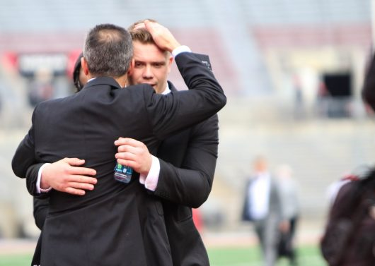 OSU coach Urban Meyer hugs OSU redshirt senior center Pat Elflein before the Buckeyes' 30-27 win over Michigan. Credit: Alexa Mavrogianis | Photo Editor