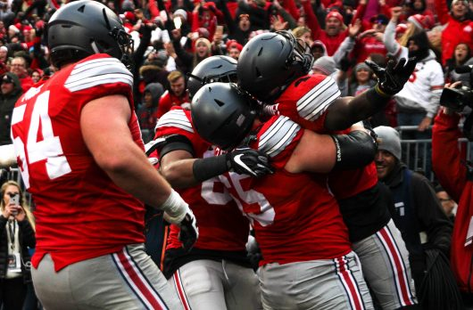 OSU junior offensive lineman Pat Elflein (65) lifts OSU junior H-back Curtis Samuel (4) following Samuel's game winning touchdown in the second overtime against Michigan. Credit: Alexa Mavrogianis | Photo Editor