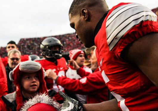 OSU junior linebacker Raekwon McMillan (5) is congratulated by a young fan following the Buckeyes' 30-27 overtime win against Michigan on Nov. 26. Credit: Alexa Mavrogianis | Photo Editor