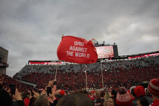 Fans wave a flag on the field after the Buckeyes' game against Michigan on Nov. 26 at Ohio Stadium. The Buckeyes won 30-27. Credit: Mason Swires | Assistant Photo Editor