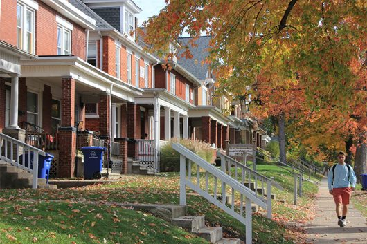 A student walks to class past the large multi-bedroom houses and red-leaved tress that line East 18th Avenue. Credit: Nick Roll | Campus Editor