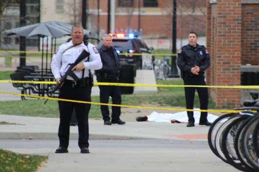 A police officer and two other emergency personnel stand near a body lying near the Chemical and Biomolecular Engineering Chemistry building on North Campus. Credit: Mason Swires   Assistant Photo Editor