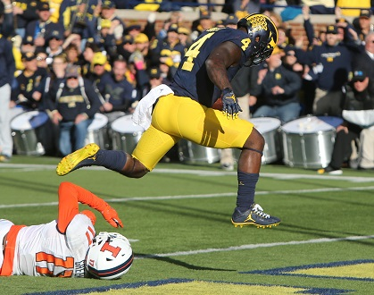 Michigan running back De'Veon Smith (4) goes over Illinois defensive back Stanley Green for a touchdown on Saturday, Oct. 22, 2016, at Michigan Stadium in Ann Arbor, Mich. Michigan won, 41-8. Credit: Courtesy of TNS