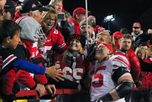 OSU senior offensive lineman Pat Elflein (65) poses for pictures with fans after the Buckeyes 62-3 win against Maryland on Nov. 12.