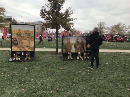 A Buckeye fan stops before one of the murals featured in Eyes of Freedom: Lima Company Memorial on Nov. 26. Credit: Elizabeth Suarez | Multimedia Editor