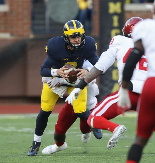 Michigan quarterback John O'Korn is pressured by Indiana defenders during the Wolverines' game against Indiana on Nov. 19. Credit: Courtesy of TNS