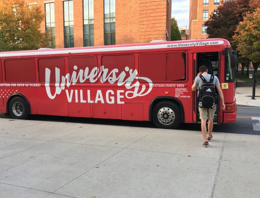 A student boards the University Village bus that transports residents of the complex to and from campus. Credit: Mitch Hooper | Engagement Editor