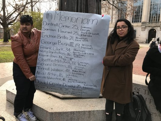 Set up on the Oval on Dec. 7, Students hold up a list of names of people of color killed by police. Credit: Elizabeth Suarez | Multimedia Editor