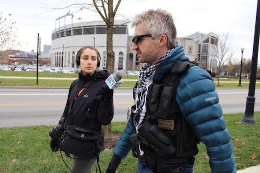 An open-carrying protester speaks with a WOSU reporter while walking past The 'Shoe on Dec. 5.Credit: Nick Roll | Campus Editor