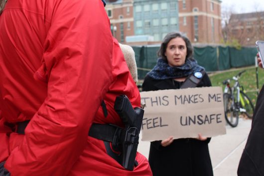 Merrill Kaplan, a professor in the English and Germanic departments discusses gun rights with openly carrying protesters on campus. Credit: Nick Roll   Campus Editor