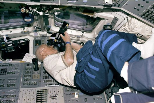Payload Specialist John Glenn takes photos from a Discovery flight deck window on his third day of flight. Credit: Courtesy of NASA