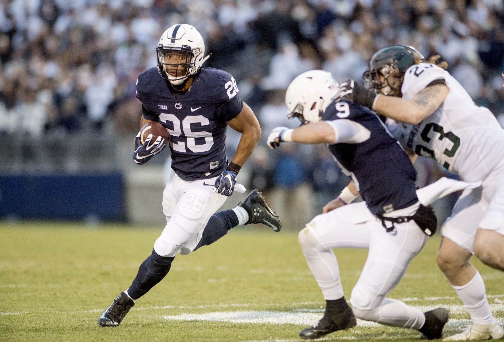 Penn State running back Saquon Barkley (26) runs down the field with the  ball as quarterback Trace McSorley (9) blocks Michigan State linebacker  Chris Frey ... 437446651