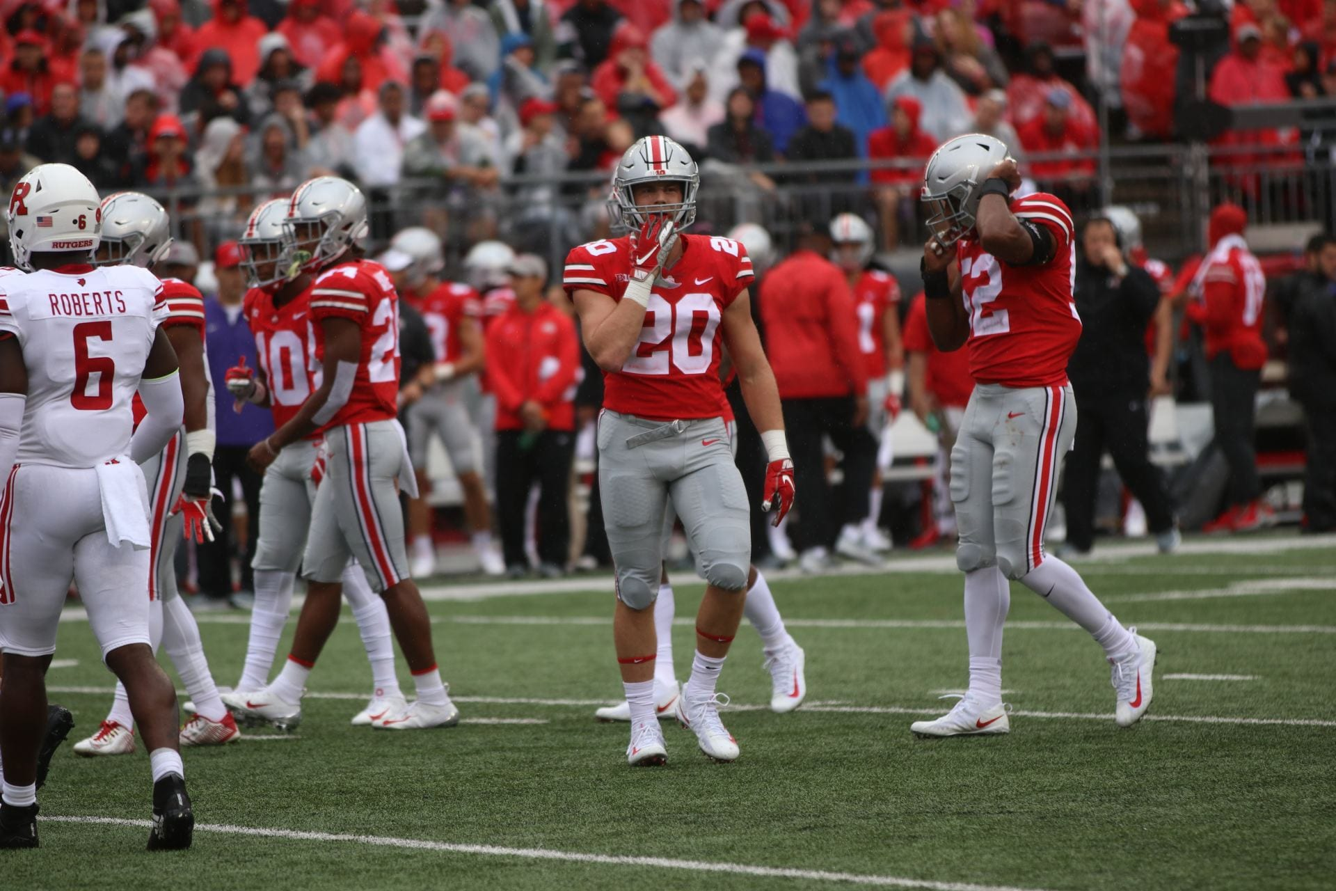 Pete Werner walks on the field at Ohio Stadium with teammates in the background