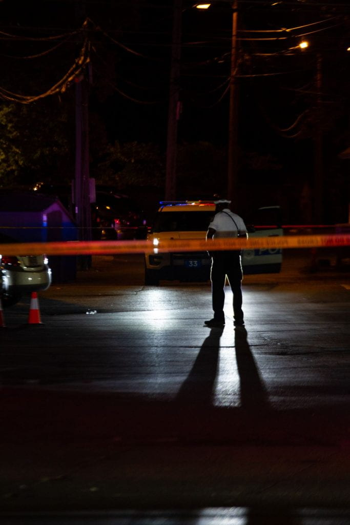 An officer stands where a witness said an altercation occurred between four men before shots were fired. Credit: Jack Long | Special Projects Director