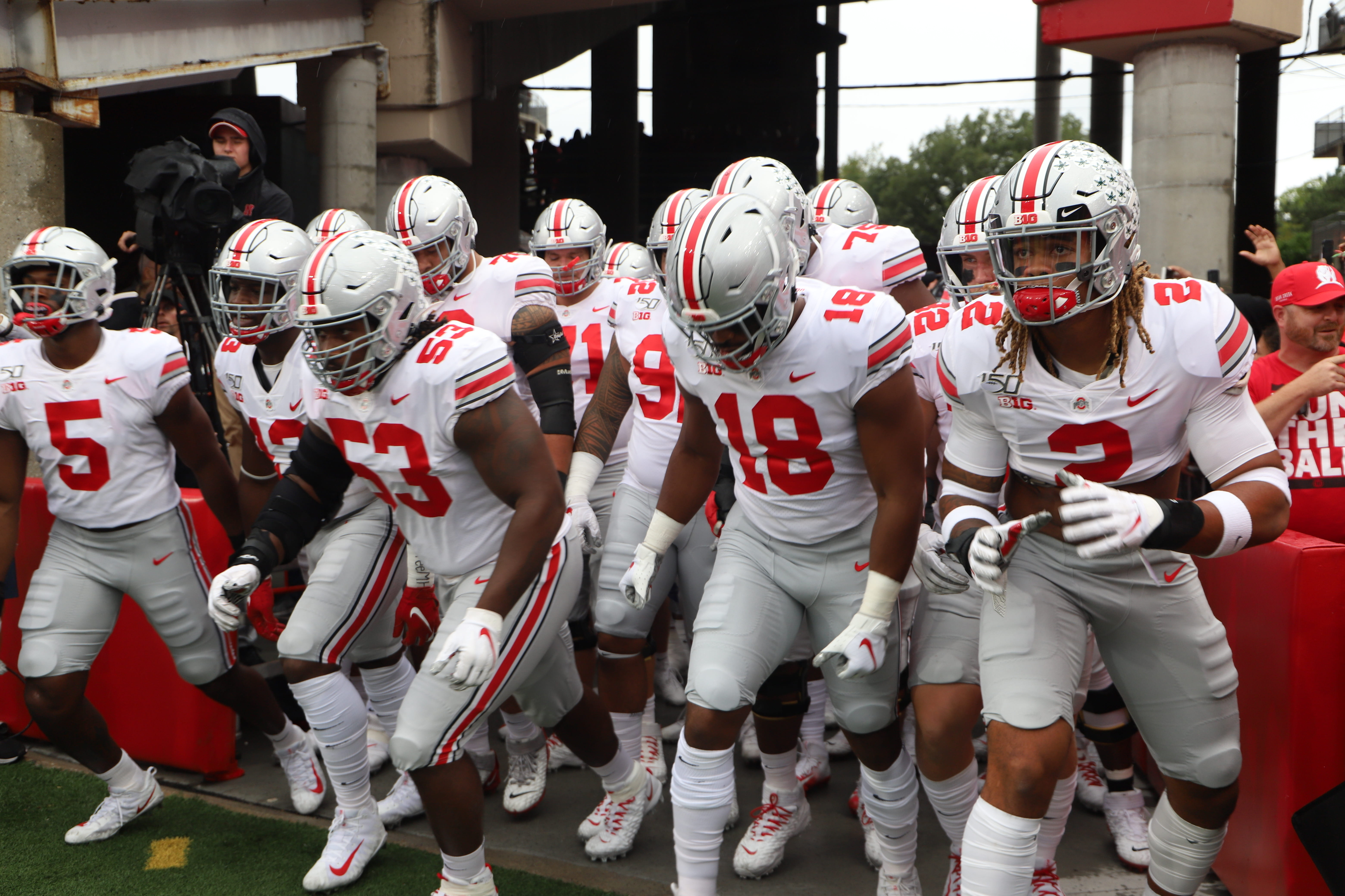 Ohio State football players run onto the field to warm up before the road game against Nebraska.