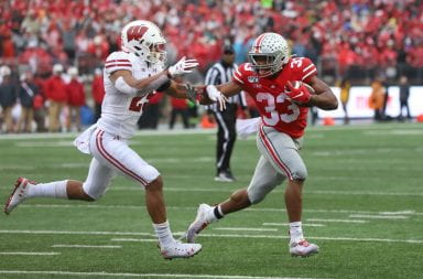 Ohio State running back Master Teague stiff-arms a Wisconsin defender