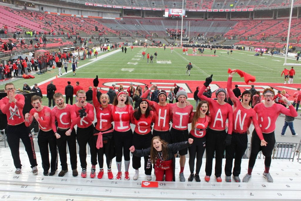 A line of students with chests painted red spell out Muck Fichigan