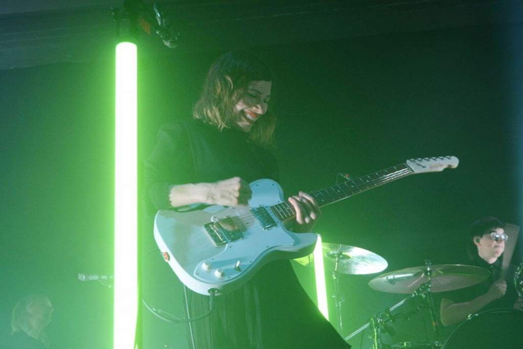 "Carrie Brownstein of Sleater-Kinney smiles down at her guitar while performing ""Price Tag"" at Newport Music Hall on Nov. 1. Credit: Rachael Crouch 
