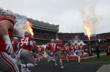 Ohio State football players running out onto to the field in front of scarlet crowd in Ohio Stadium.