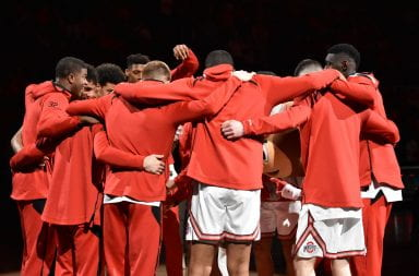 Ohio State men's basketball team huddle together at mid-court under a spotlight before a game