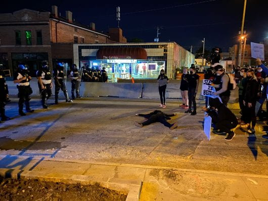 A protester lays on the road between police and a group of protesters on North High Street, south of Fifth Avenue. Credit: Max Garrison | Asst. Campus Editor
