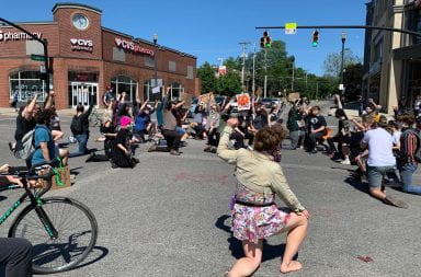 Protestors kneel on Lane and High