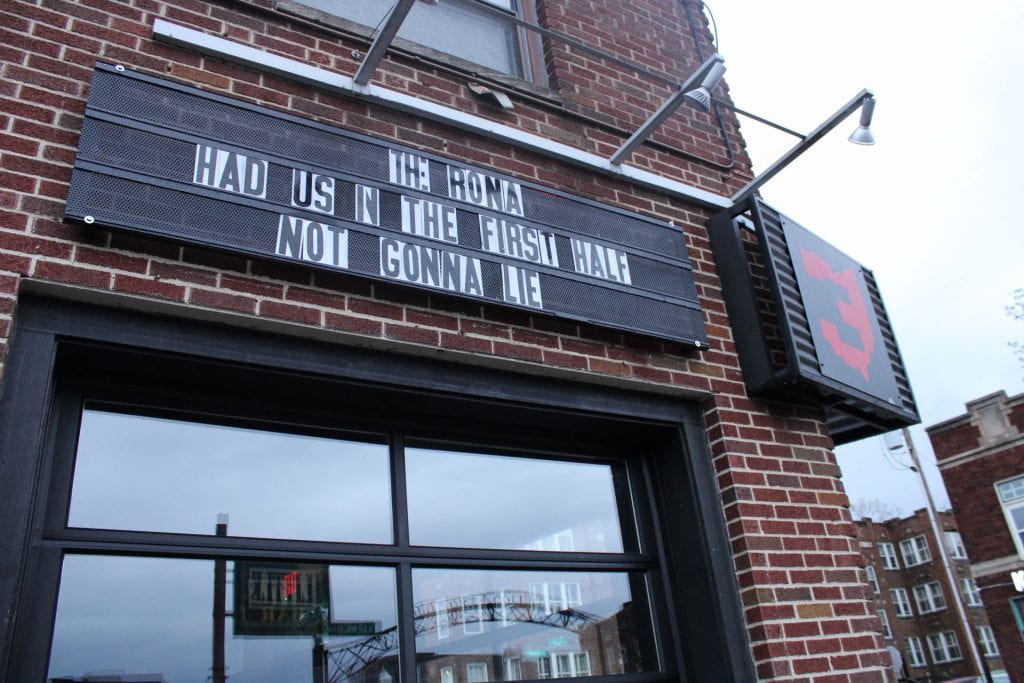 """Storefront of Threes Above High with a sign reading """"The Rona had us in the first half not gonna lie"""""""
