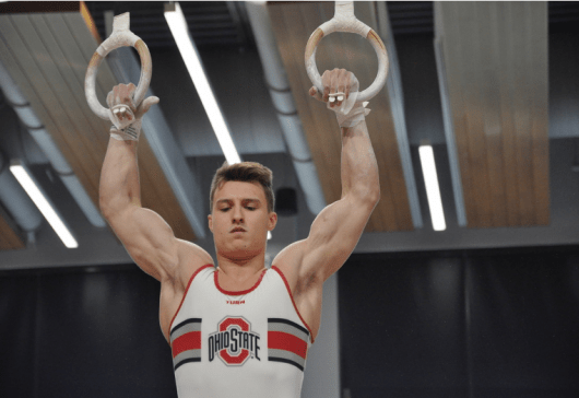 Ohio State junior Max Andryushchenko takes the rings in the Covelli Center on Feb. 29 for the meet against Navy at the Covelli Center. Credit: Alyssa Jacobs | For the Lantern
