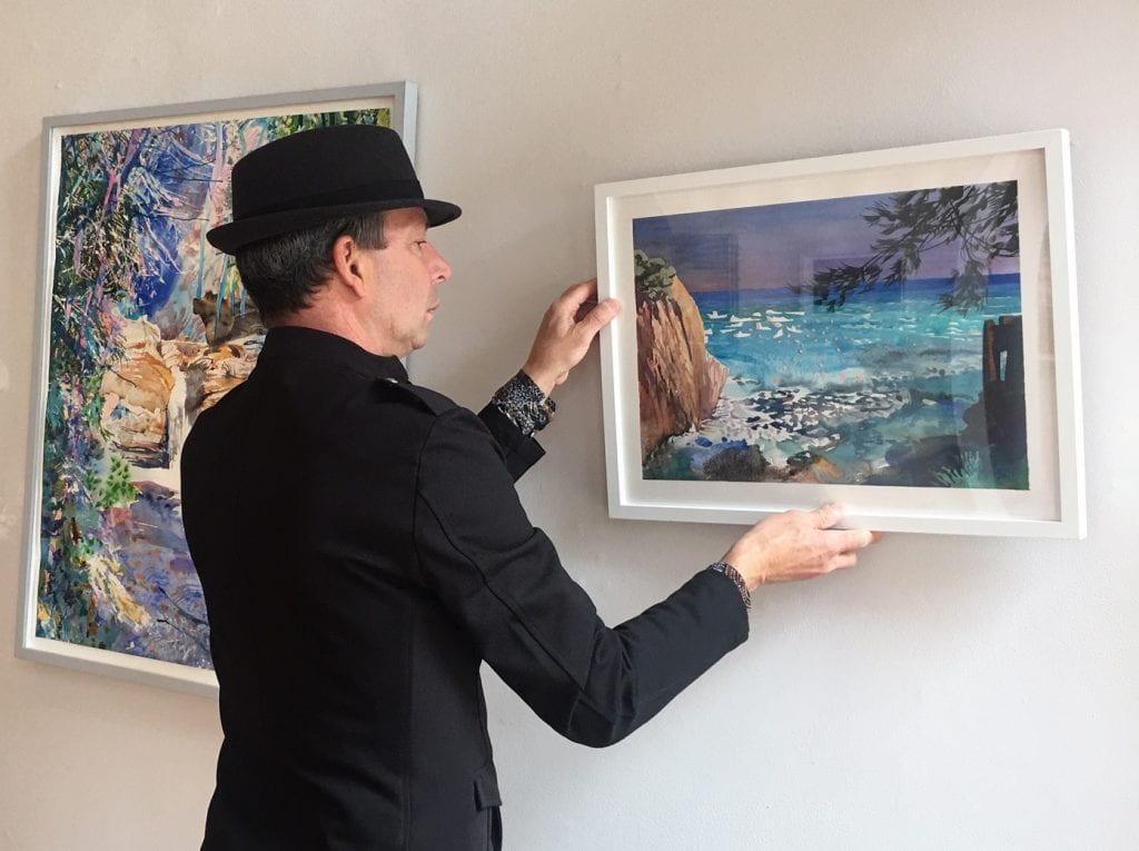 Michael Kaiser hangs a photo