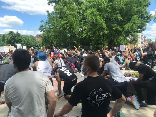 Protesters kneel in honor of George Floyd in downtown Cincinnati at Washington Park. | Courtesy of Amna Rustom