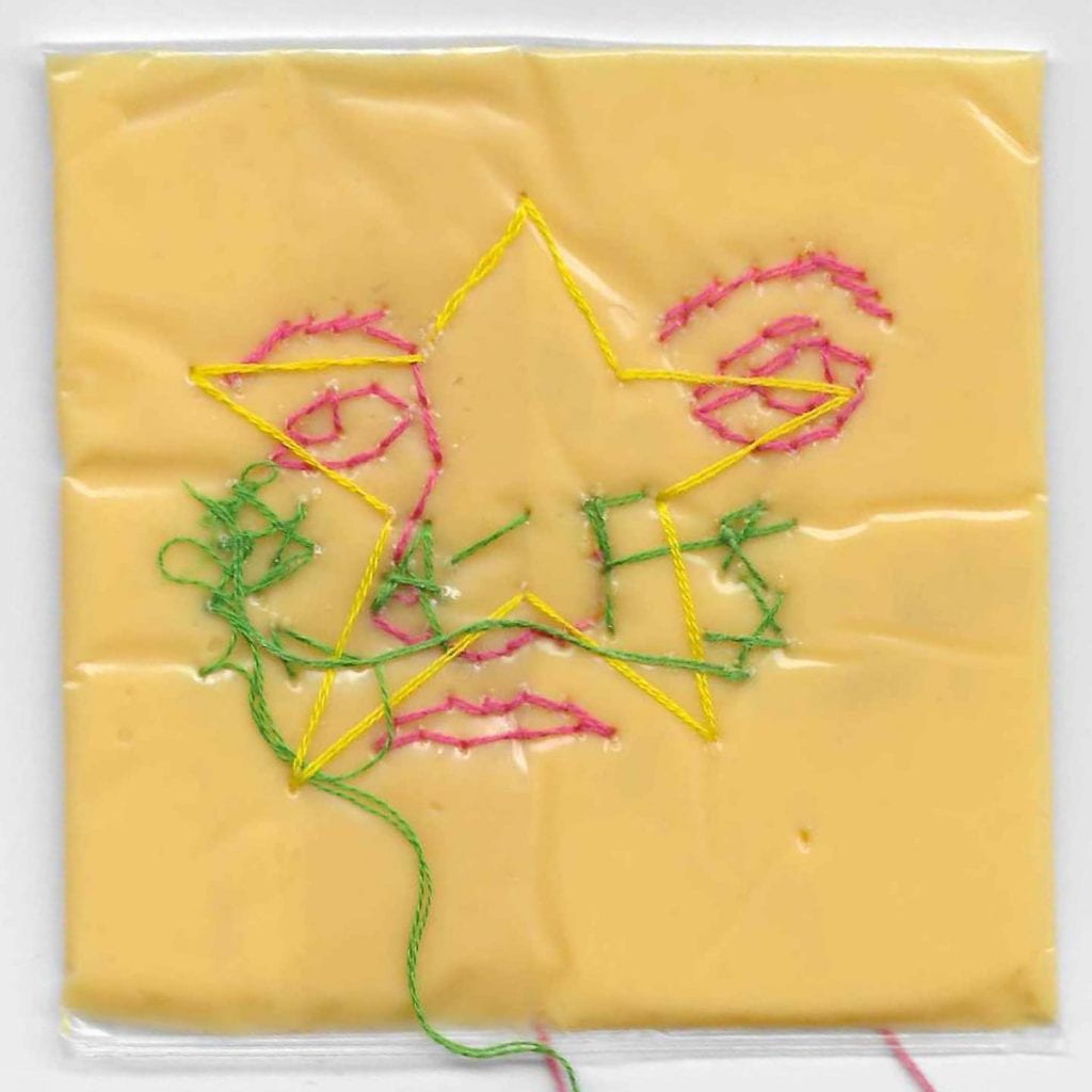 A slice of American cheese with sewed thread forming a face