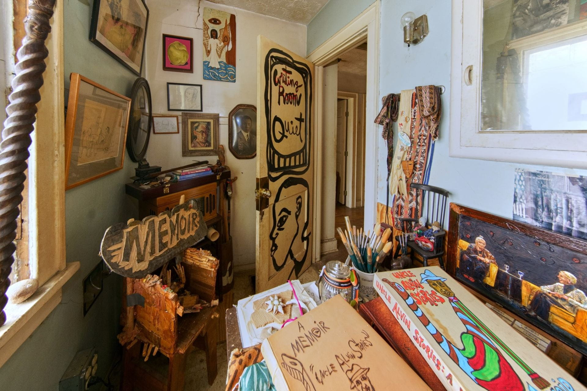 A small room with walls covered with paintings and artwork