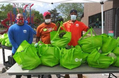 Three volunteers hold green bags full of produce to distribute to needy families.